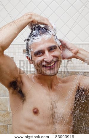 Hispanic man shampooing hair in shower