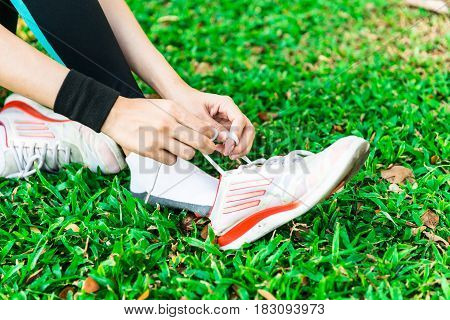Young Asian Female Runner Sitting Down Putting Shoe Lace Together
