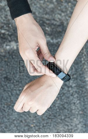 Young Asian Female Runner Putting On Heart Rate Monitor Wrist Watch Band Smart Wearable Device