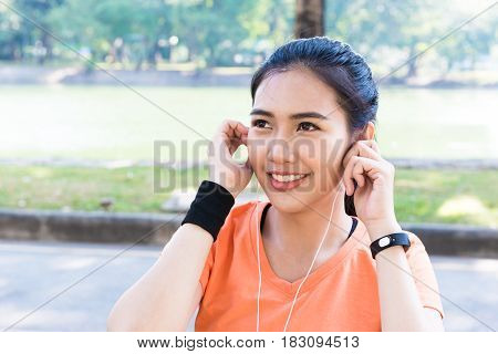 Young Beautiful Attracttive Asian Female Runner Listening To Music From Smart Phone With White Ear P