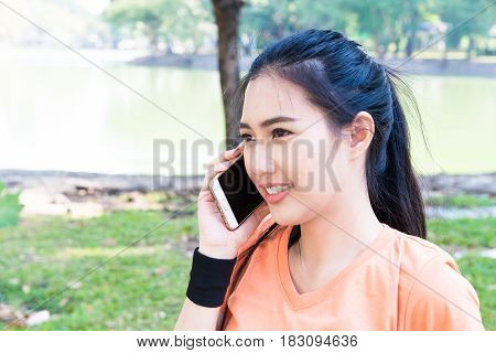 Young attractive Asian female runner talking with smart phone for communication exercise in the morning for healthy sport running exercise summer spring sunny day concepts