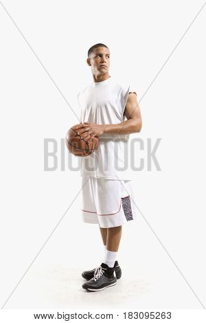 Mixed race basketball player holding ball