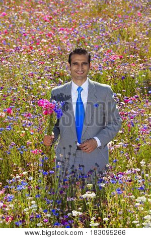 Hispanic businessman holding bouquet in field of wildflowers