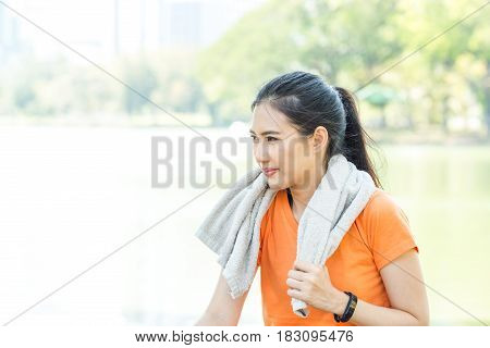 Portrait Of Attractive Confident Smile Young Asian Woman Runner With Orange Shirt Sport Watch Holdin