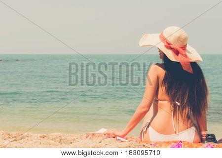 Beautiful Asian Bikini Woman Sitting On Beach Looking Into Sea