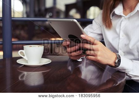 Cropped shot of woman on lunchtime with reading latest news on tablet and having a cup of strong espresso