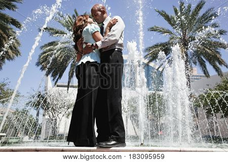 Couple hugging and kissing at fountain