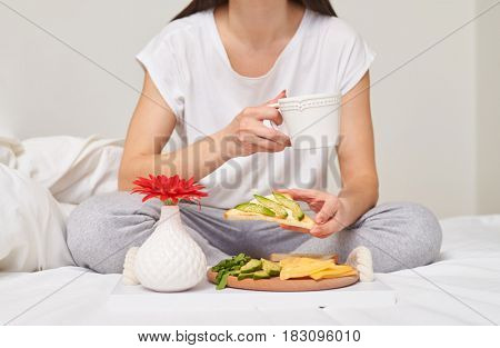 Cropped shot of woman in pajamas drinking tea and eating sandwich with cheese, avocado sitting in the bed with copy space