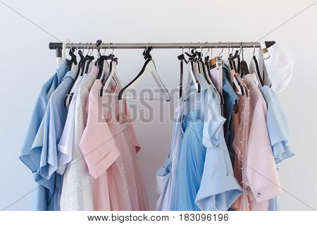 Side view of different female clothing on hangers on background of white wall.
