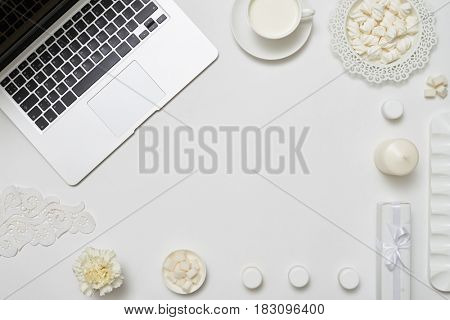 Top view shot of a workspace with open laptop, flower, marshmallows and a cup of milk on white background