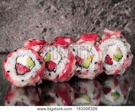 Tuna scallop roll with strawberry and avocado over gray concrete background
