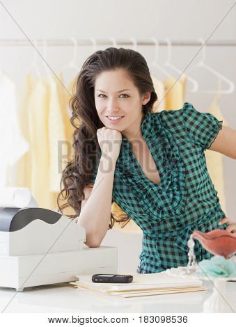 Mixed race woman leaning on cash register