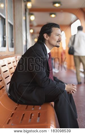 Mixed race businessman on bench and looking pensive