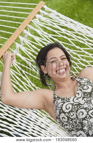 Hispanic woman laying in hammock
