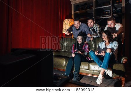 Group of youth have fun playing video game, competition at home. Two girls with joysticks on couch, three guys cheer emotionally, free space