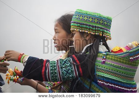 Sa Pa, Vietnam - March 15, 2017: Unidentified Hmong childrens in Sapa, Vietnam trying to sell their colorful handicrafts in the city
