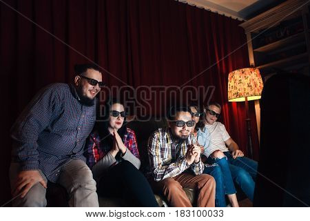 Company of five young happy friends in 3d glasses on couch watch movie on tv at home. Fun, entertainment, leisure, home theatre concept