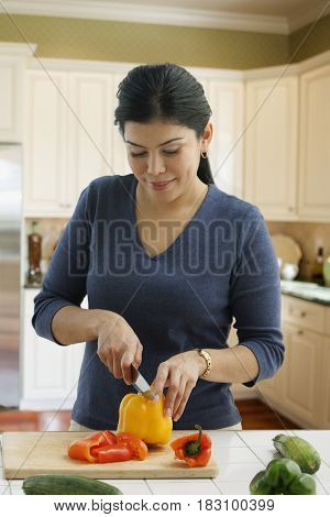 Hispanic woman slicing bell pepper