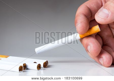 Man's hand holding cigarette above white table. Nicotine and tobacco addiction abstract concept.