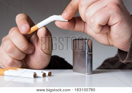 Young man breaking cigarette. Quitting nicotine and tobacco addiction abstract concept.