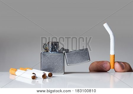 Young man holding broken cigarette. Quiting nicotine and tobacco addiction abstract concept. Copy space on the top.