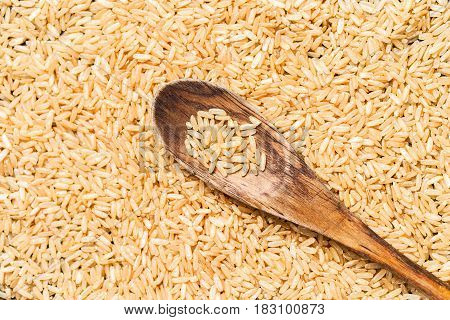 Top view of brown rice in a wooden spoon
