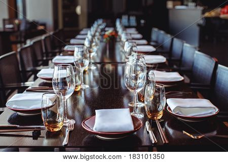 Dark table set with tableware and glassware for reception in restaurant.