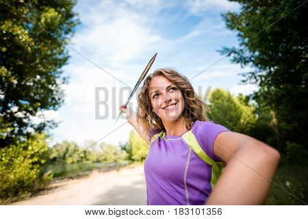 Wide angle view of a young smiling woman throwing a javelin - outdoors during training
