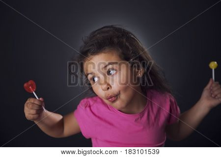 Expressive Little Girl With Lollipops