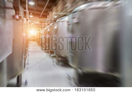 Modern Beer Factory. Small steel tanks for storage and fermentation of beer. Motion blur effect, sunlight