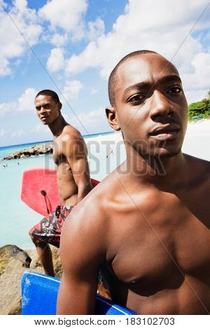 African men holding body boards on beach