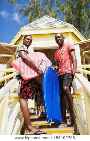 African men holding body boards