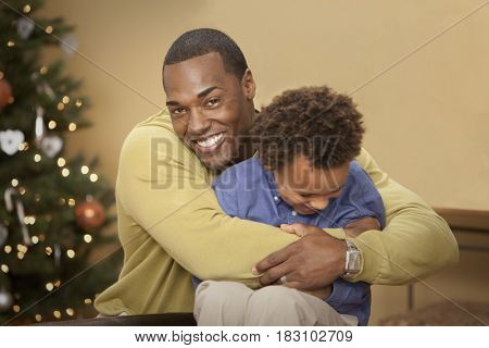 Father and son hugging near Christmas tree