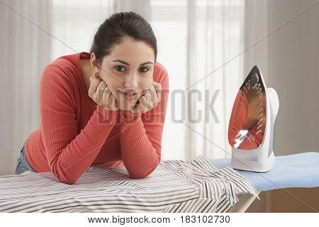 Mixed race woman ironing shirt