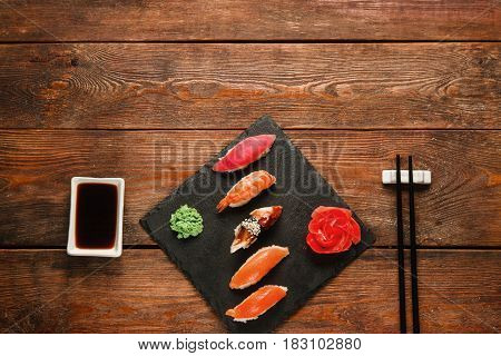 Tasty delicious set of five sushi nigiri served on black slate with ginger and wasabi, on wooden rustic table, flat lay. Japanese cuisine, dark background with free space.