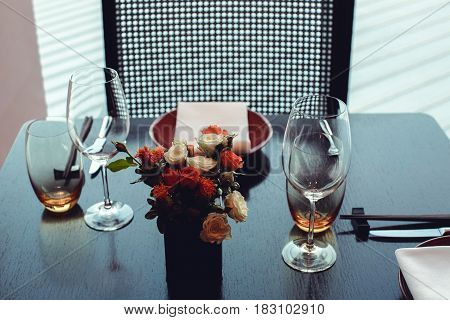 Close up of wooden table set with glassware and decorated with flowers.