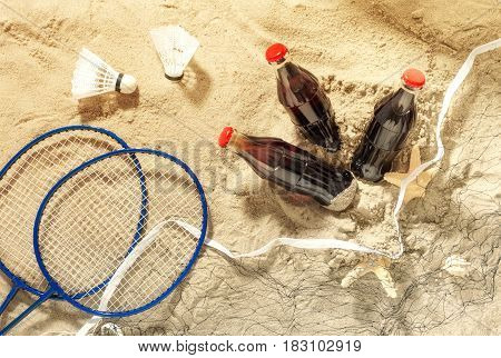 Three bottles of cool drink with rackets for playing badminton on sand top view. Summer background