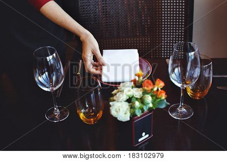 Crop waitperson in black uniform serving table with wineglass in restaurant on blurred background.