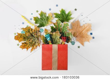 Red gift box with colorful autumn dry leaves party confetti candles and noisemakers on a white background. Flat lay top view. Colorful holiday background