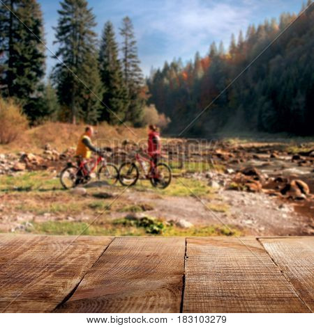 Empty wooden table in the background of the forest with couple of cyclists for product display montage