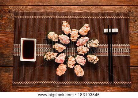 Set of appetizing fresh gunkan sushi rolls served on brown straw mat, flat lay. Japanese national seafood, restaurant menu photo, food art.