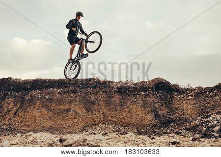 Male biker in sportswear jumping of rock.
