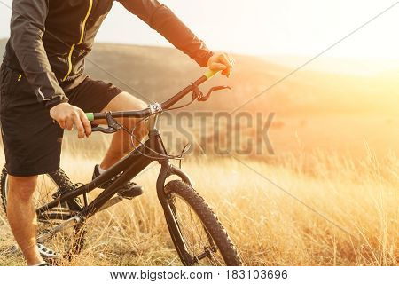 Crop faceless man sitting on mountain bike among field and mountains in sun light.