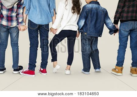 Group of children holding hand together in rear view
