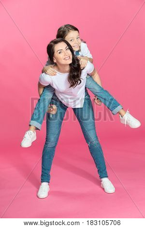 Happy Mother Piggybacking Adorable Little Daughter Smiling At Camera