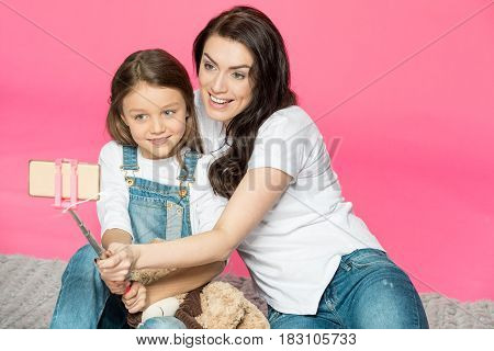 Beautiful Happy Mother And Daughter Sitting Together And Taking Selfie