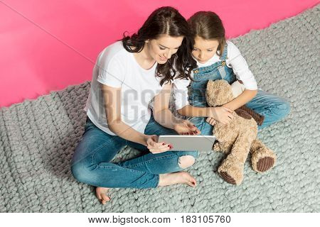High Angle View Of Mother And Daughter With Teddy Bear Sitting And Using Digital Tablet