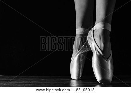 Close-up Classic Ballerina's Legs In Pointes On The Black Floor