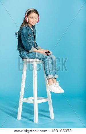Adorable Little Girl In Headphones Using Smartphone And Sitting On Stool In Studio On Blue