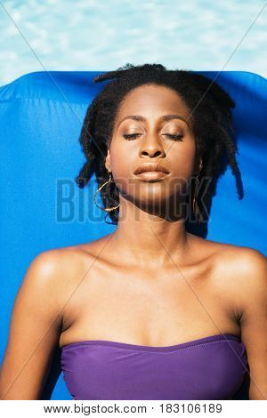 African woman sunbathing with eyes closed